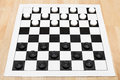 Starting position on vinyl draughts board x wooden table Stock Images
