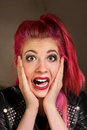 Startled woman with pink hair young punk rocker female hands on face Stock Photography