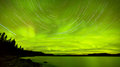 Startrails northern lights show over lake laberge astrophotography star trails with green glowing display of aurora borealis or Royalty Free Stock Photos
