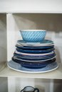 Stash of blue plates in a cabinet different types Royalty Free Stock Photo