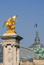 Statue at the alexandre iii bridge over the seine in paris with the grand palais in the rear Royalty Free Stock Images