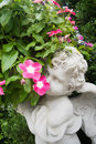 Statue of an angel holding a rose sitting on a tombstone in a ce Royalty Free Stock Photo