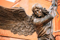 Statue of archangel michael with outstretched close up detail wings thrusting spear into dragon before catholic church st Stock Images
