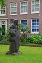 Statue of a Beguine in the beautiful courtyard of The Begijnhof at Amsterdam Royalty Free Stock Photo