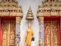 Statue of buddha in abhaya mudra posture with tiered umbrella a thai temple Stock Image