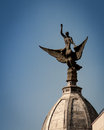 Statue on building in madrid of man riding winged creature domed rooftop spain Stock Image