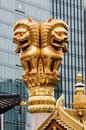 Statue of a golden lion on the roof of a Buddhist temple against the backdrop of a modern building Royalty Free Stock Photo