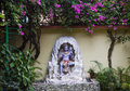 Statue of Hindu Lord Shiva under the beautiful blooming tree, Rishikesh. India Royalty Free Stock Photo