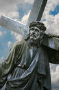 A statue of jesus carrying the cross on sky background Stock Photography
