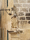 Statue of jesus looking down on triq is sur this medieval in the old city mdina the corner a building bastion street Stock Photo