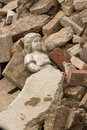 Statue laying in rubble discarded of girl Stock Photos