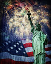 Statue of liberty and fireworks composite photo the with a usa flag in the background nice patriotic holiday image for Royalty Free Stock Photos