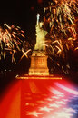Statue of Liberty with fireworks and U.S. flag Stock Photography