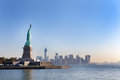 The statue of liberty free of tourists and new york city downtown on sunny early morning Stock Images