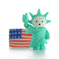 Statue of liberty miniature with us flag Royalty Free Stock Photography
