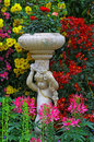 Statue of a little cherub in a tropical garden Royalty Free Stock Photo