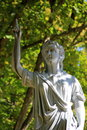 Statue with long flowing robes under shady tree figure of dressed in holding stone cross pointing finger towards heaven Stock Image