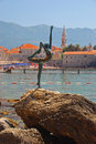 Statue of naked dancing girl on a rock with budva old town in the background and mountain Royalty Free Stock Photo
