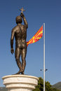 Statue in ohrid macedonia a of a man holding a cross with the macedonian flag the background Stock Photo