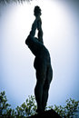 Statue of an olympic athlete holding a torch silhoutted against a blue sky in park barcelona Royalty Free Stock Image