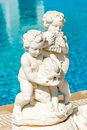 Statue at the side of a swimming pool two boys holding fish and playing on flute Royalty Free Stock Photo