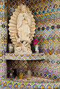 Statue of virgin mary with mosaic tile background and candles in foreground Stock Photos