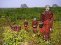 Statues of buddhist monks in the forest mawlamyine myanmar hundreds collecting alms surround massive win sein taw ya buddha Stock Image