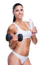 Stay hydrated beautiful young woman in white bra and panties holding bottle with water and dumbbell while standing isolated on Stock Image