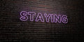 STAYING -Realistic Neon Sign on Brick Wall background - 3D rendered royalty free stock image