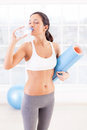Staying refreshed attractive young woman in sports clothing drinking water while holding an exercise mat in sport club Royalty Free Stock Image