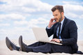 Staying in touch anytime and everywhere confident young man formalwear working on laptop talking on mobile phone while sitting on Royalty Free Stock Image