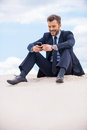 Staying in touch cheerful young businessman looking at his mobile phone and smiling while sitting on sand and against blue sky Stock Images