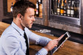 Always staying in touch confident young man shirt and tie sitting at the bar counter and working on digital tablet Royalty Free Stock Photos
