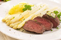 Steak with asparagus as closeup on a white plate Royalty Free Stock Photos