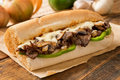 Steak and cheese sub a delicious oven baked submarine sandwich with mushrooms green peppers onion Stock Photos