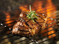 Steak cooking over flaming grill with rosemary garnish Royalty Free Stock Images