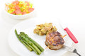 Steak dinner on white high key image of grilled plate and background with bright back light tossed salad potatoes and asparagus Royalty Free Stock Photography