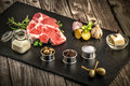 Steak, fresh meat oo stone plate, gastronomy, garlic and onion, spice, rosemary with meat, butter, wood table, additives, preparat Royalty Free Stock Photo
