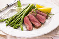 Steak with green asparagus slices as closeup on a white plate Royalty Free Stock Images