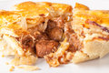 Steak and kidney pie on a plate cooked with brown pastry cut open to show meat filling of close up version Stock Image