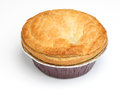 Steak meat pie on white background in aluminium foil tray focus centre of pastry top Stock Photography