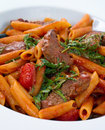 Steak and pasta penne in arabiatta sauce with slices rucola close up shot Royalty Free Stock Images