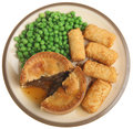 Steak pie meal isolated on white individual with croquette potatoes peas and gravy Stock Photos