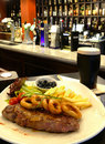 Steak and a pint of dark beer garnished with in bar Stock Image