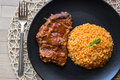 Steak with tomato sauce and bulgur rice in a black plate. Royalty Free Stock Photo