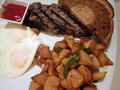 Steak with two eggs over easy two slices of rye bread potatos and cup ketchup on square plate knife on table Stock Photos