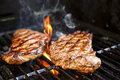 Steaks on barbecue beef cooking in open flame grill Royalty Free Stock Images