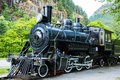 Steam engine train locomotive an old sits on sits on tracks in the mountains Royalty Free Stock Photo