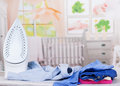 Steam iron, ironing board and clothes on background of room. Royalty Free Stock Photo