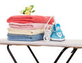 Steam iron, ironing board, towels and bouquet of roses  . Royalty Free Stock Photo